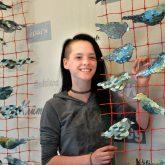 Julia mit ihrem Kunstwerk - Vogel auf Netz.