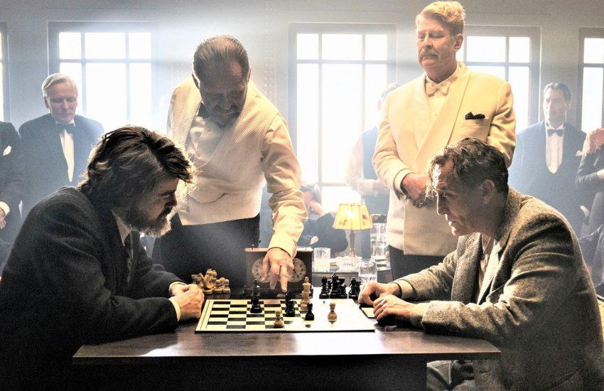 McConnor (Rolf Lassgård, hinten, rechts) bittet Bartok (Oliver Masucci, vorne, rechts) die Partie mit Czentovic (Albrecht Schuch, vorne links) weiterzuspielen (hinten, links Samuel Finzi in seiner Rolle als Alfred Koller).