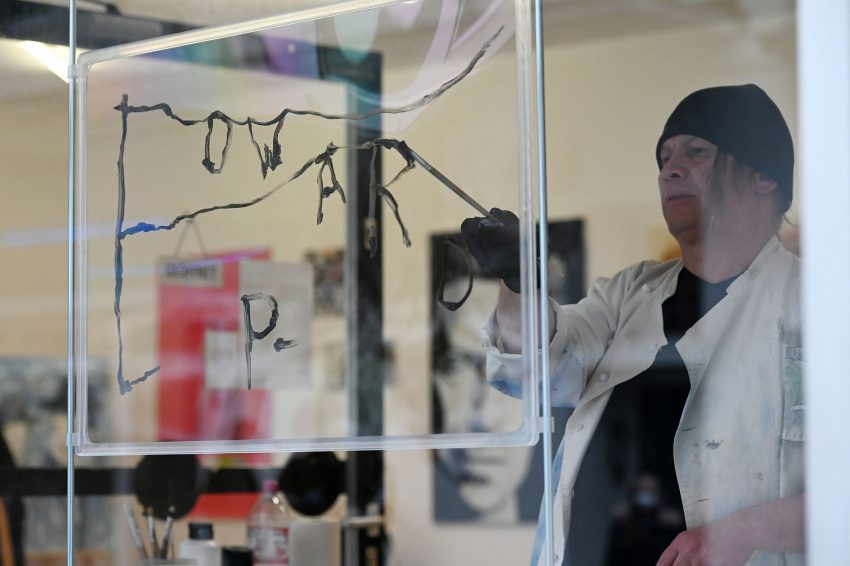Künstler Edward P. malt sichtbar auf einer Plexiglasscheibe.