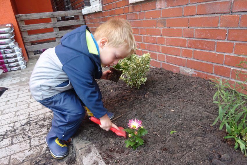 Kleine Gärtner helfen bei der Bepflanzung im Außenbereich.