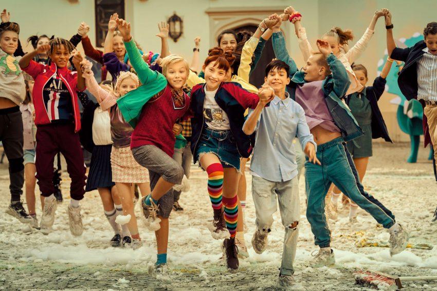 Benni (Leonard Conrads), Ida (Emilia Maier) und Jo (Loris Sichrovsky) tanzen mit der Klasse auf dem Schulhof.