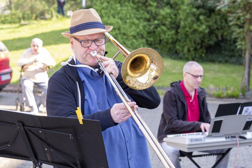 Die Musikschullehrer Gerald Gatawis und Christian Ribbe (li.), von der städtischen Musikschule in Herne (NW), musizieren für Bewohner des Eva-von-Tiele-Winckler-Altenheims, am Sonntag (12.04.2020).