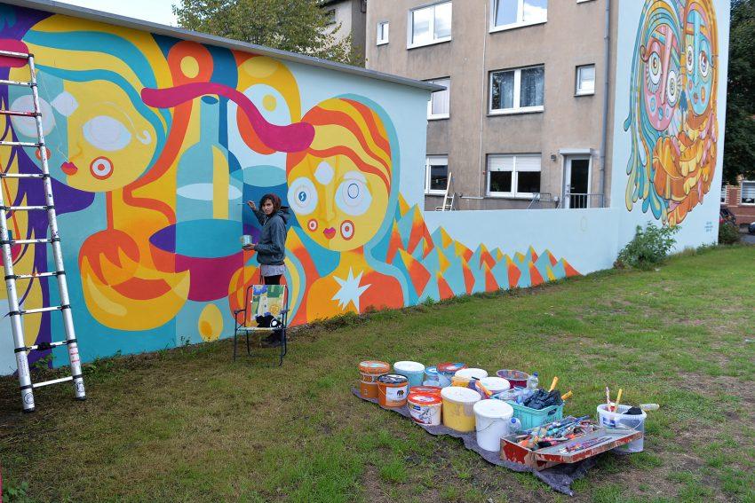 Ursula Meyer erweitert das Wandgemälde - Weltbaustelle - an der Bielefelder Straße.