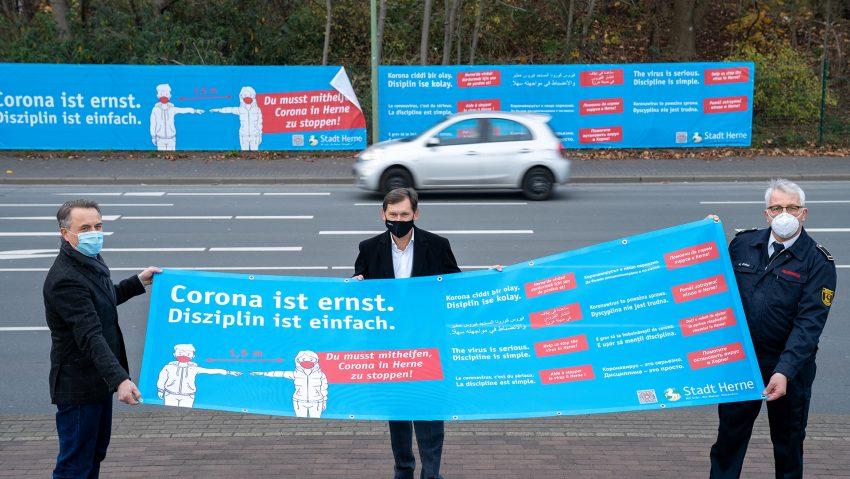 Banner und Plakate der Stadt und des Stadtmarketing, um mehr vor Corona zu warnen, v.li. Holger Wennrich, Geschäftsführer Stadtmarketing Herne, Oberbürgermeister Dr. Frank Dudda und Andreas Wolter, Feuerwehr Herne.