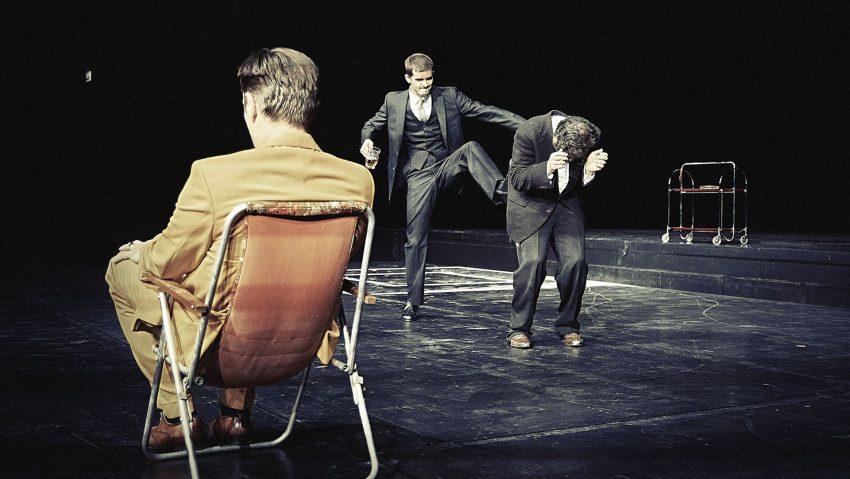 Noch gibt sich Johan Nagel (Steve Scharf. l.) unbeteiligt, als Minute (Guy Clemens, r.) vom Assessor (William Cooper) erniedrigt wird.