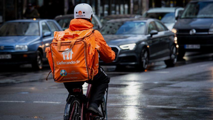 Bei Wind und Wetter unterwegs: Fahrrad-Kuriere bei Lieferando arbeiten zu niedrigen Löhnen und unter hoher Belastung, kritisiert die Gewerkschaft NGG.