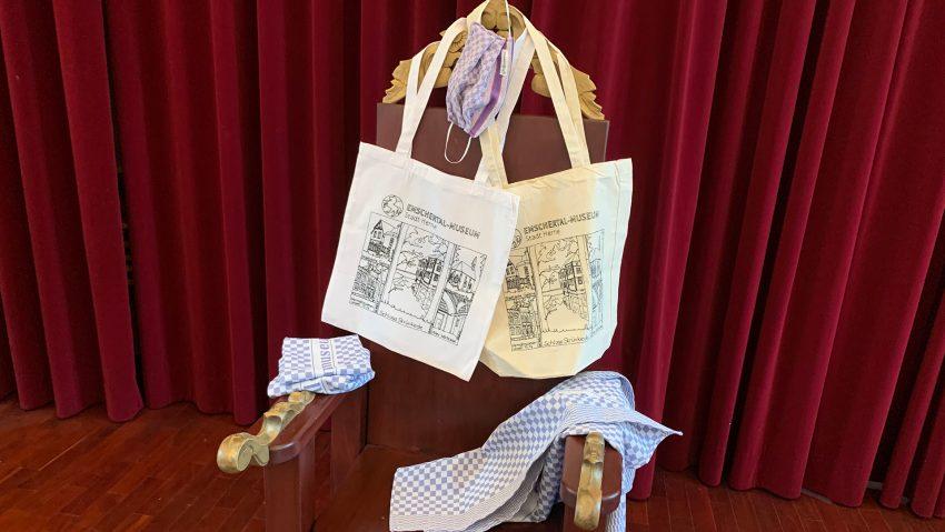 Taschen, Masken und Grubentücher hängen über dem Stuhl.