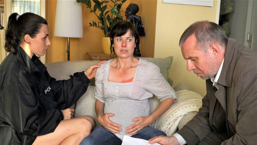 Conny Mey (Nina Kunzendorf, l.) und Kollege Frank Steier (Joachim Król, r.) sprechen mit der hochschwangeren Witwe Elsa Lange (Inka Friedrich).