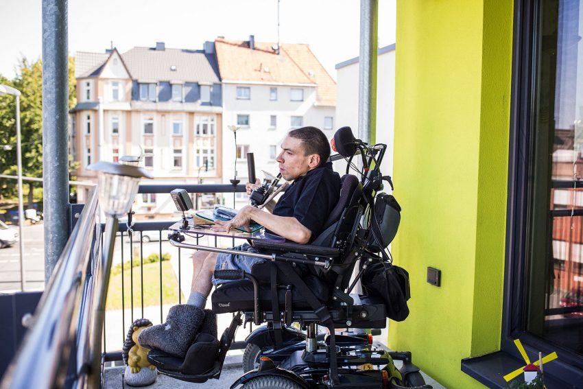 Marc Szykowiak sitzt im Rollstuhl und kann seinen Körper nicht zielgerecht bewegen. Mit ihm leben 15 weitere Menschen mit schwersten Mehrfachbehinderungen im Apartmenthaus in Bochum-Weitmar, zwar unter einem Dach, aber jeweils in einer eigenen Wohnung - selbstbestimmt und selbständig.