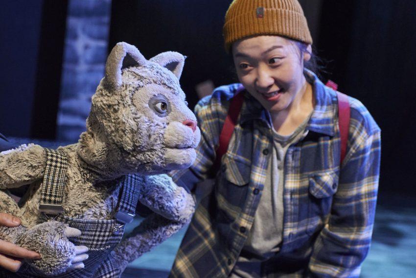 Dongmin Lee mit der Klappmaulpuppe der karierten Katze.