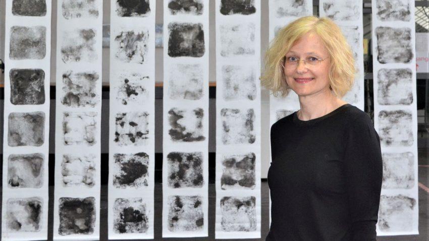 """Die polnische Künstlerin in der Schwarzkaue vor ihrem großformatigen Monoprint auf Banner """"Von der andere Seite"""" aus dem Jahr 2019."""