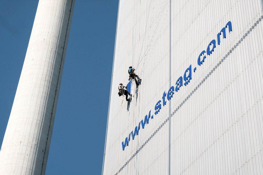 Industriekletterer bringen am Kesselhaus Block 4 der Steag AG in Baukau eine Werbetafel an.