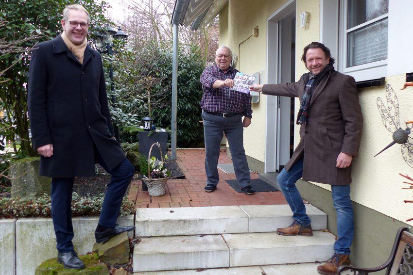 Jens Koch (r.), Geschäftsführer der Diakonie Ruhr, und Superintendent Gerald Hagmann überreichen die Dankesschrift an Werner Neveling.