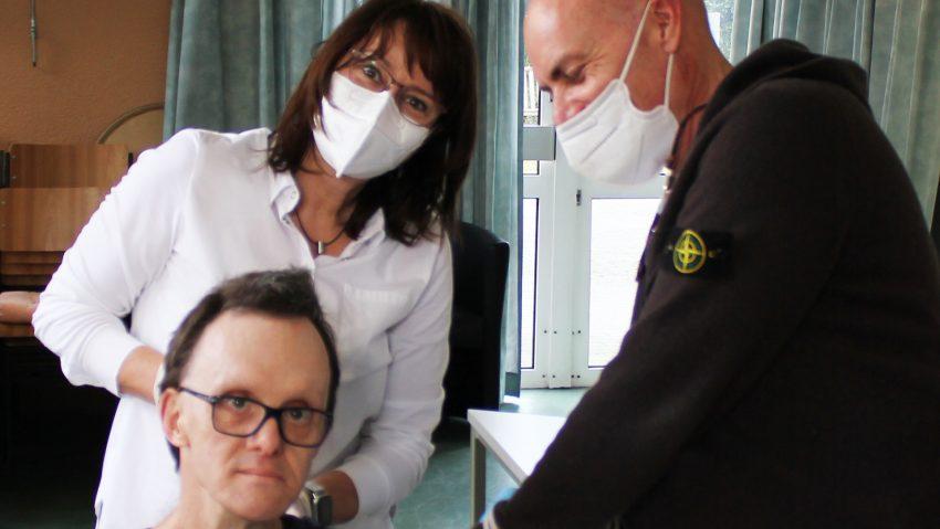 Endlich gut geschützt: Hausarzt Dr. Markus Bruckhaus-Walter (re.), unterstützt von Arzthelferin Birgit Albers, versorgt Haus1-Bewohner der Lebenshilfe Herne, Bernd Kriege, vor Ort mit dem Moderna-Impfstoff.