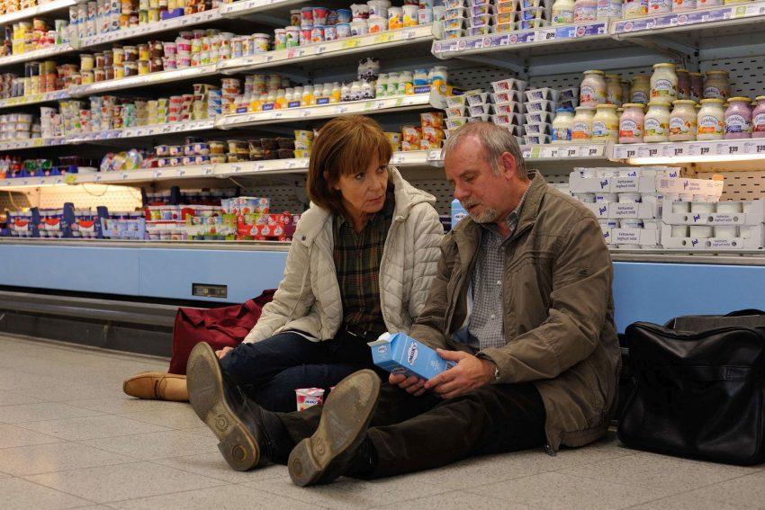 Der Bankraub. Vor dem Milchregal im Supermarkt erfährt Helga (Ulrike Kriener) von ihrem Mann Werner Kreye (Joachim Król) die finanzielle Lage nach dem Börsencrash.