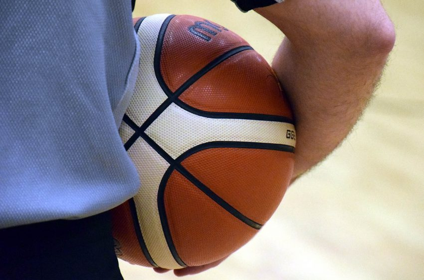 Basketball in Schiedsrichterhand.