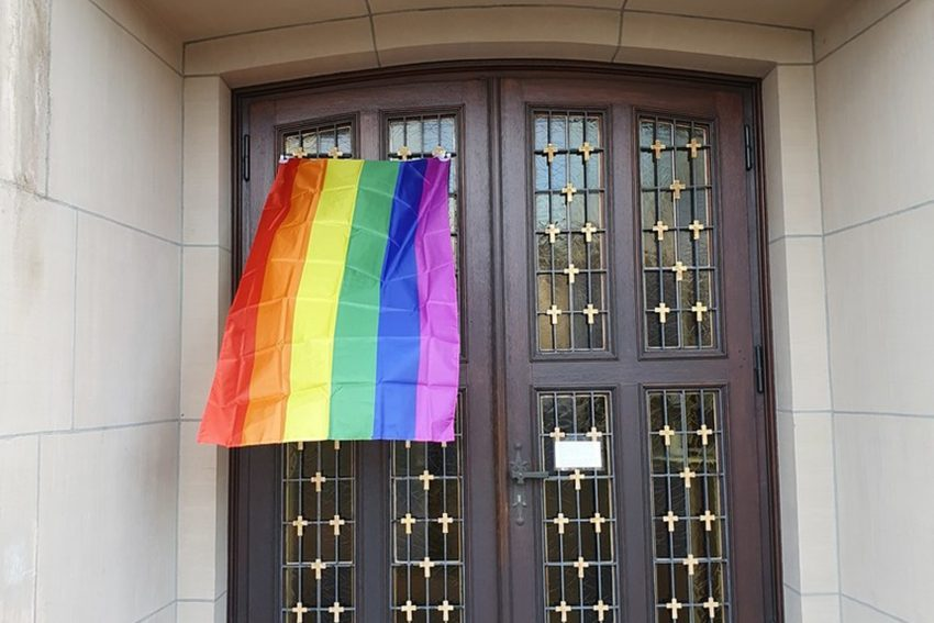 Die Regenbogenfahne an der Kirche der Gemeinde Hl. Familie, sie weht als Symbol der gleichgeschlechtlichen Liebe und der Geschlechterdiversität.