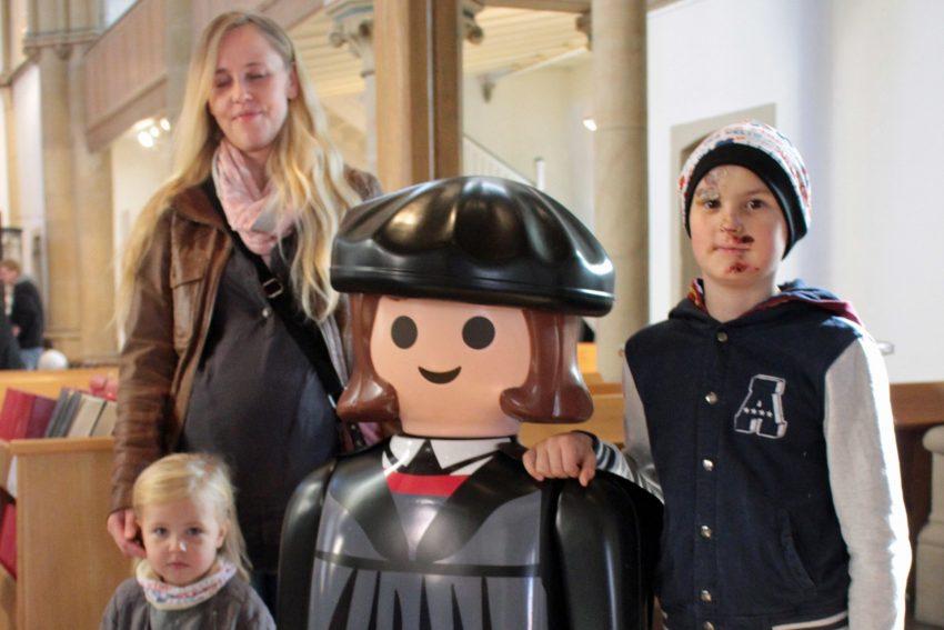 Die Luther-Playmobil-Figur mit Kirchenbesuchern.