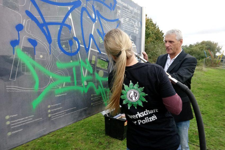 Polizistin beim Graffiti Entfernen.