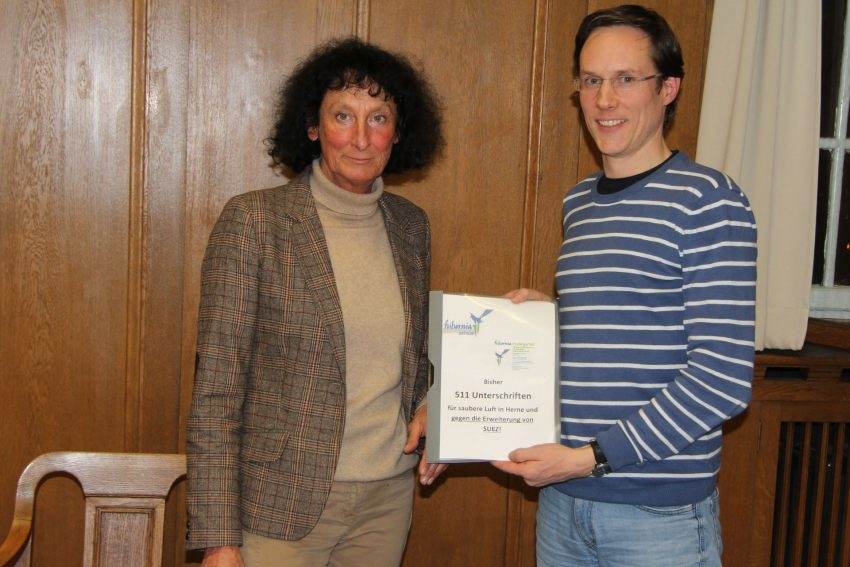 v.l. Barbara Merten (Umweltausschuss) nimmt von Daniel Fey (Elternbeirat Hibernia) eine Mappe mit 511 Unterschriften gegen die SUEZ-Erweiterung an.