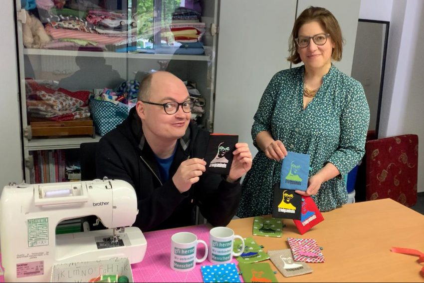 Die Künstlergruppe 'Erfolgsminute' bei der gfi: Chiara bringt Marc das Nähen mit einer Nähmaschine bei.