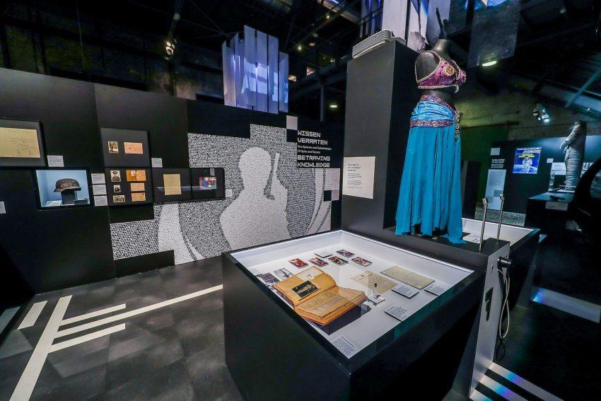 Blick in die Ausstellungseinheit zur Spionage. Links hinten in der Vitrine Hasenjaegers Helm mit den Einschusslöchern.