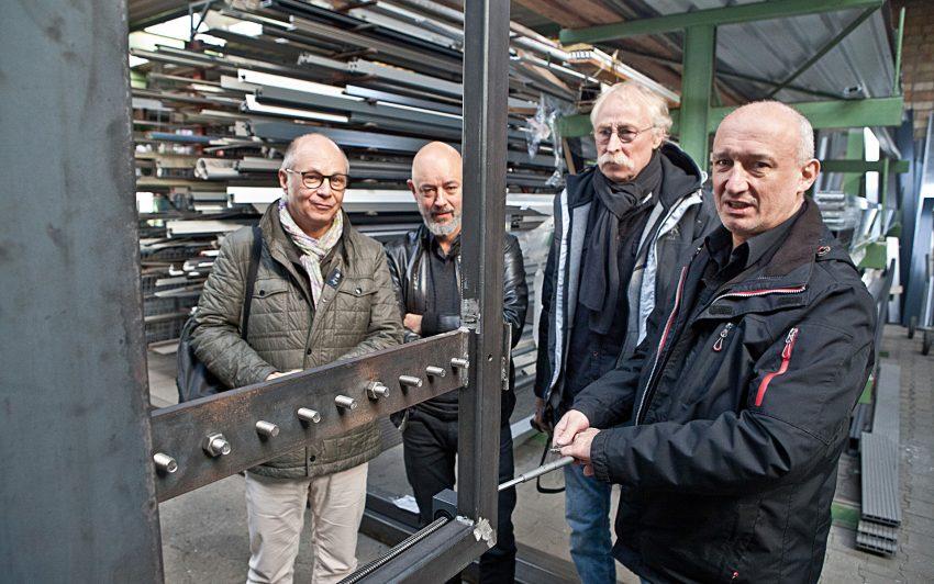 Ulrich Graeve vom Gebäudemanagement testet das Schneckengetriebe. Dieter Röber (Statiker), Dirk Godau (Architekt) und der Künstler Winfried Venne beobachten den Vorgang genau.
