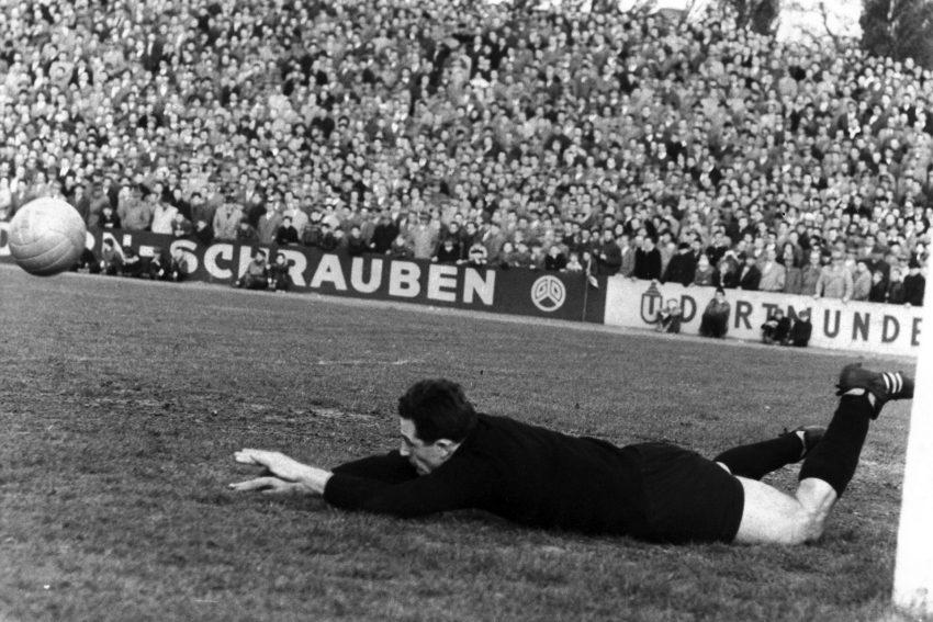 """Hans Tilkowski im Stadion am Schloss Strünkede, 1959. Im Hintergrund ist die Bandenwerbung von """"Dorn-Schrauben"""" zu erkennen. Tilkowski absolvierte dort seine Ausbildung."""