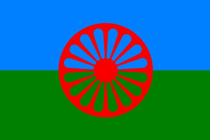 Die Roma-Flagge: Blau steht für den Himmel, grün für die Erde – ein Ausdruck der Naturverbundenheit der Roma. Das als Chakra erkennbare Rad verweist auf die indische Herkunft.