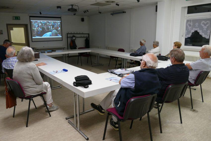Klaus Lamche (li) zeigt Heimatfreunden einen historischen Film zur Cranger Kirmes.