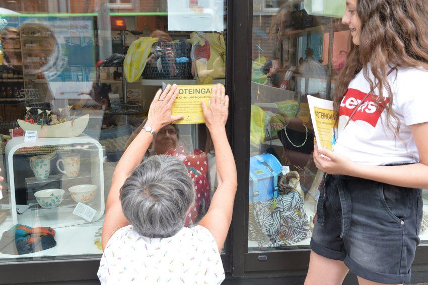Christa Winger vom Weltladen 'Esperanza' bringt das Schild der Aktion 'Noteingang' an der Scheibe des Weltladens an.